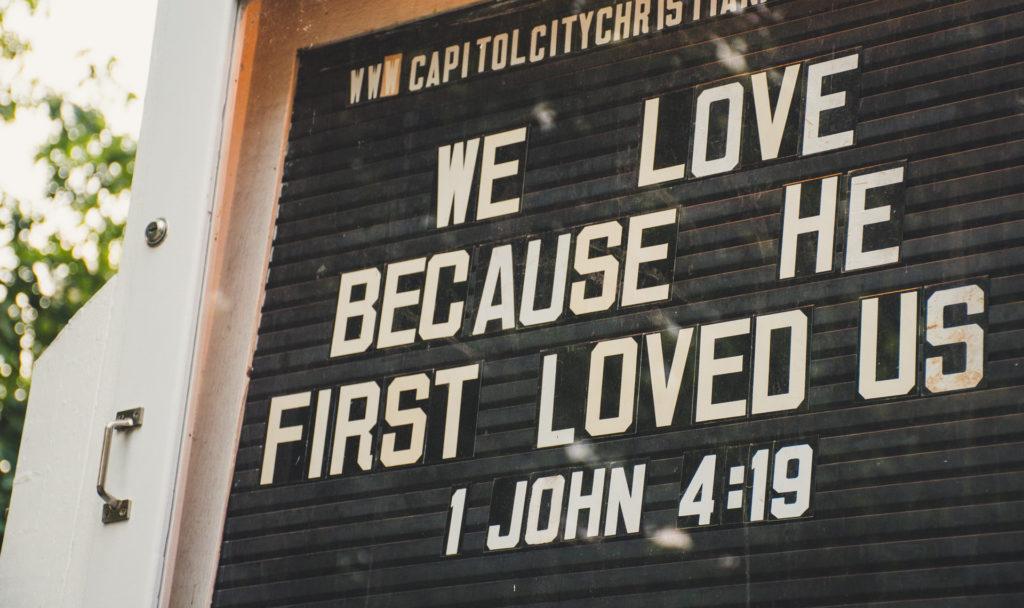 church sign with 1 John 4:19